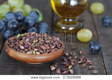Grape seed in wooden bowl. Antioxidant, healthy grape seed oil and fresh grape on the table. Closeup view.