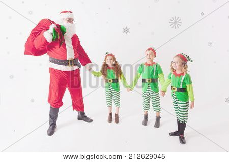 Santa's helpers are working at North Pole, elves and kids holding gift boxes. Merry Christmas. Santa sitting at many gift boxes and reading wishes list. Letters To Santa Claus. Wish list