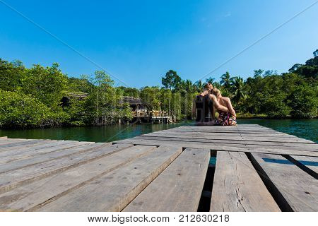 Summer landscape on tropical koh Kood island in Thailand. Young caucasian couple sitting on pier taken from Ao Noi beach during honeymoon.
