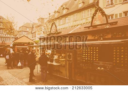 COLMAR FRANCE - NOV 23 2014: Vintage effect over Christmas Market of Colmar Alsace with tourists and locals buying gifts and sweets