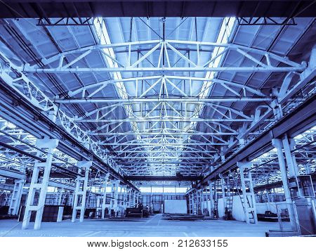 Unified standard typical span prefabricated of a reinforced concrete frame production building. Industrial indoors view in blue tone.