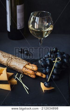 Cheese plate served with crackers grapes and glass of white wine on dark background. Old gouda cheese on tasting plate