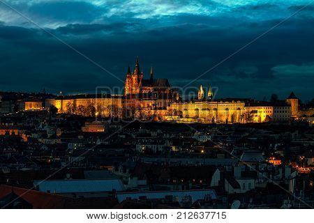 View of illuminated Saint Vitus cathedral and roofs of Old Town in Prague, Czech Republic.