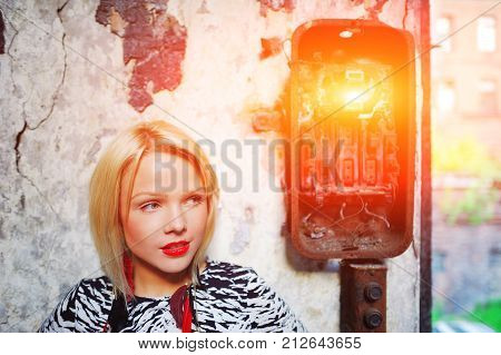 Portrait of a young attractive blonde girl with bright make-up on the background of a shabby old wall with rusty broken electrical panel in close proximity.