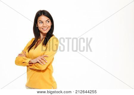 Portrait of a smiling young woman standing with arms folded and looking away at copy space isolated over white background