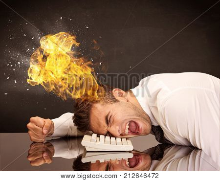 A depressed businessman banging his head in a keyboard and shouting with his head on fire, reflecting on desk