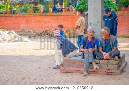 BHAKTAPUR, NEPAL - NOVEMBER 04, 2017: Unidentified people at outdoors sitting in the enter of ancient Hindu temple in the Durbar square in Bhaktapur, this is the city with more temples for area.