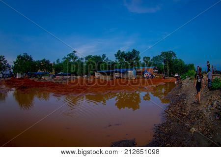 CHITWAN, NEPAL - NOVEMBER 03, 2017: Unidentified people walking close to a street with dirty water, happy tourists for jungle safari at Chitwan National Park, Nepal, fish eye effect.