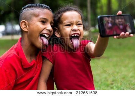 Siblings taking selfie photos in the park