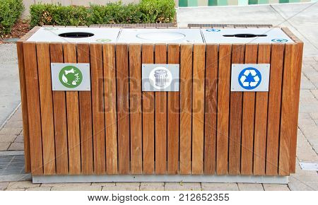 Wood enclosure for trash cans to prevent birds and other animals from spilling and digging into the trash. Composting recycling and regular trash triple set up.