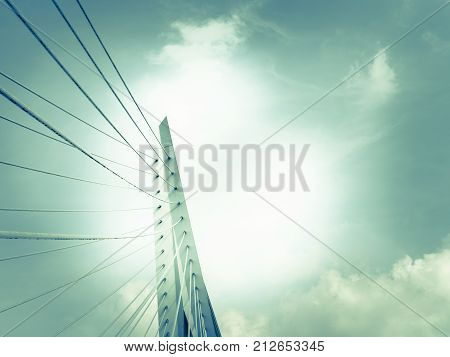 Erasmus Bridge bright white structure and stays backlit by late afternoon sun and cloudy sky monochrome retro effect blue faded tones.