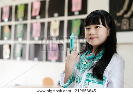 Asian girl playing as doctor occupation in kindergarten class kid occupation education concept