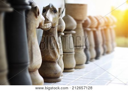 Funny face on knight of chess made from wooden. Face to face knight of chess with toothy smile. selective focus and warm light effect
