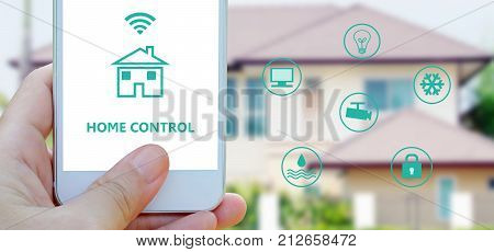 Hand using smart phone as smart home control application over blurred house background banner smart home concept the internet of things