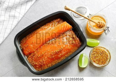 Dish with salmon fillet in honey mustard marinade on table