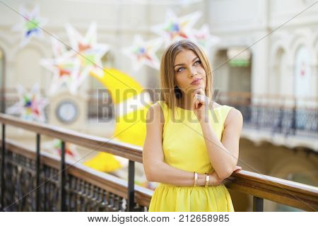 Portrait close up of young beautiful happy woman in yellow dress dress