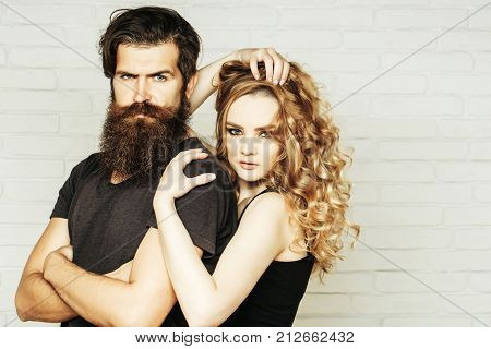 Fashion beauty style concept. Girl and bearded hipster. Hipsterism subculture trend. Man with beard and woman with long blond hair. Couple in love hug on white brick wall.