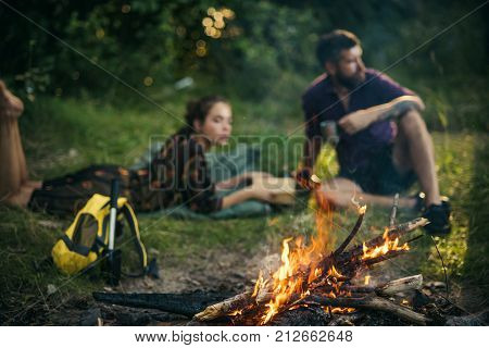 Bonfire flame burn and blurred man woman relax on nature on natural landscape. Bio energy ecology environment concept.
