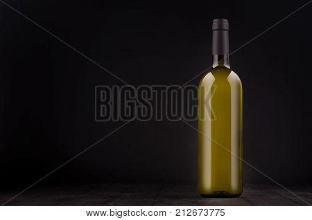 Green bottle of white wine mock up on elegant dark black wooden background copy space. Template for portfolio advertising design branding identity cover magazine bar and restaurant menu.