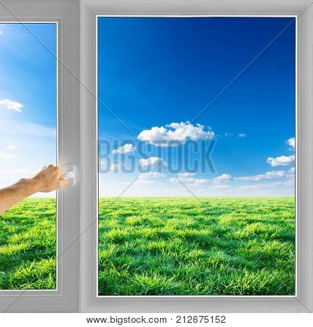 Hand open window over field nature background