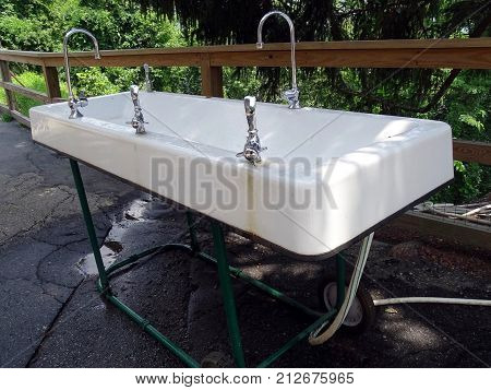 A mobile outdoor sink facility including water and drinking fountain. poster
