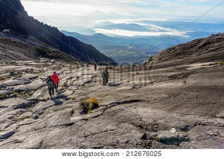 Ranau,Sabah,Borneo-March 13,2016:Mountain Climbers carefully stepping down on the granite rocky mountain from Low's Peak to Sayat Sayat check point after successfully completed conquering the mountain Kinabalu at Sabah,Malaysia.