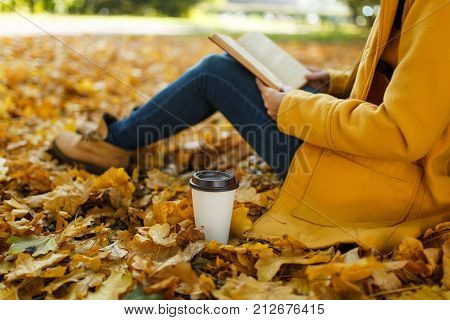 Woman In Yellow Coat, Jeans And Boots Sitting Under The Maple Tree With A Red Book And Cup Of Coffee