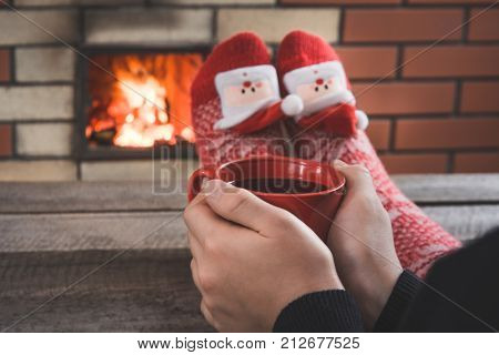 Red Cup Of Coffee In Female Hand By The Fireplace. Female Relaxes By Warmfire In Christmas Red Socks