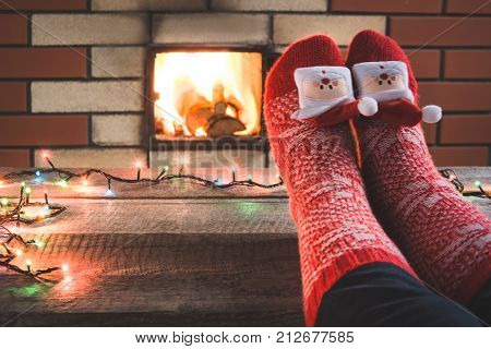 Feet In Woollen Red Christmas Socks By The Fireplace. Close Up On Feet. Tabletop For Display Your Ch