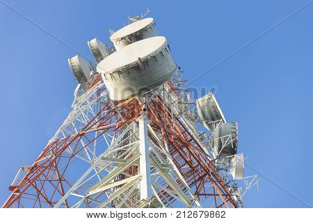 Telecommunication mast TV antennas wireless technology with blue sky in the morning, Antenna communications tower