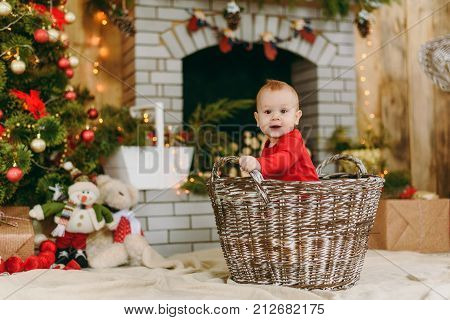 Portrait Of Playful Happy Cute Little Baby Boy, Who Sits In The Basket In A Decorated Room At Home.