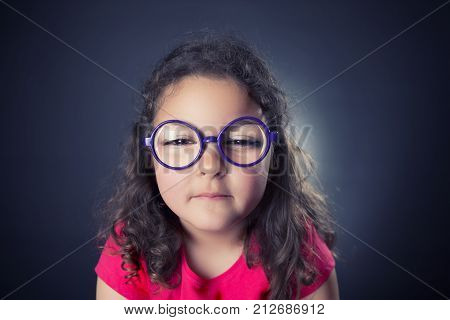 Caricature of six years girl with glasses and a myopic problem. Studio shot. Black background
