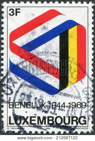 LUXEMBOURG - CIRCA 1969: A stamp printed in Luxembourg is dedicated to the 25th anniversary of the signing of the customs union of Belgium Netherlands and Luxembourg shows Mobius Strip in Benelux Colors circa 1969