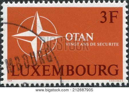 LUXEMBOURG - CIRCA 1969: A stamp printed in Luxembourg is dedicated to 20th anniversary of the North Atlantic Treaty Organization or NATO shows the symbol NATO circa 1969