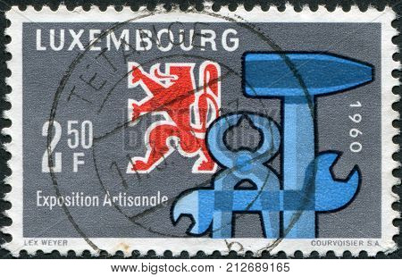 LUXEMBOURG - CIRCA 1960: A stamp printed in Luxembourg is dedicated to the National Exhibition of Craftsmanship Luxembourg-Limpertsberg shows Heraldic Lion and Tools circa 1960