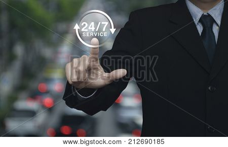 Businessman pressing button 24 hours service icon over blur of rush hour with cars and road Full time service concept