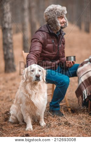 A guy in a hat and brown jacket sits on a chair and drinks a hot drink near to the dog. Gold retriever and his owner in the autumn forest
