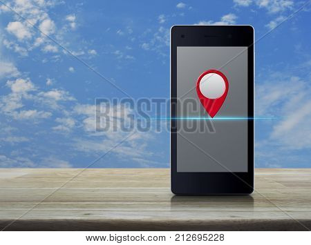 Map pin location button on modern smart phone screen on wooden table over blue sky with white clouds Map pointer navigation concept