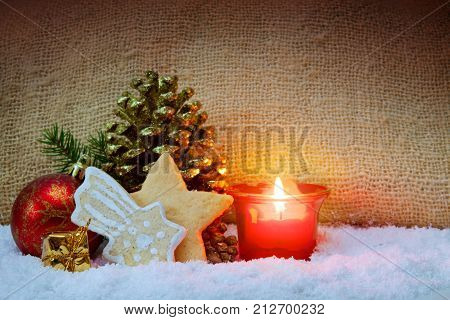 Christmas cookies and candle for Advent .Red candle with christmas ball in atmospheric light.