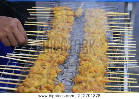 roasting chicken stab in wood on a grate