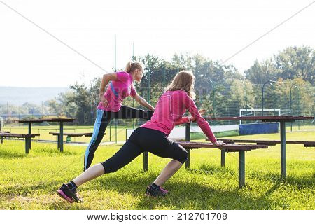 Two women doing gymnastics exercises outdoors before a workout