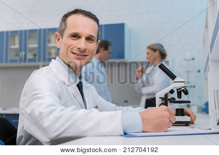 Smiling lab technician taking notes while doing microscope sample analysis