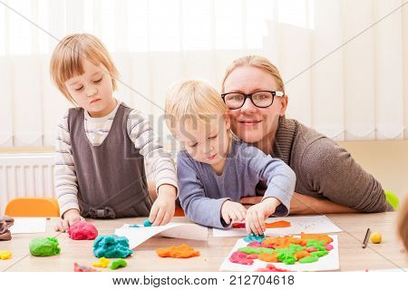 The teacher helps the boy to make a figure plasticine on the table