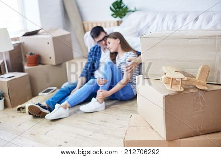 Handsome young man embracing his pretty girlfriend while sitting on floor of new apartment and dreaming about their cohabitation, piles of moving boxes and interior design items