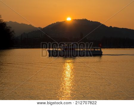 SWITZERLAND LUCERNE - MARCH 23 2015: Sun setting behind mountain at Lake Lucerne in Switzerland