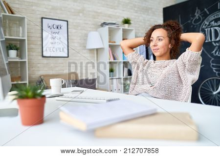 Portrait of pretty mixed race woman relaxing smiling happily sitting back at desk in modern apartment