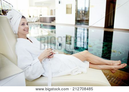 Side view portrait of beautiful young woman smiling at camera relaxing in lounge chair by swimming pool wearing bath robe