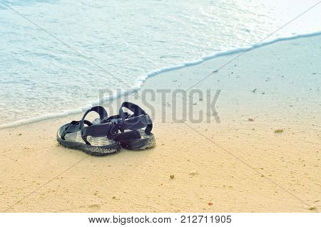 pair of black sandal on beautiful golden sand beach background with golden light on tiny wave in the morning concept is belong together and go to the dream like as sunrise or the lover in valentines.