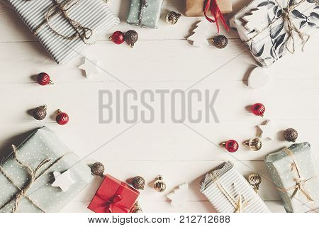 Christmas Flat Lay. Present Boxes With Ornaments On White Wooden Background Top View, Space For Text