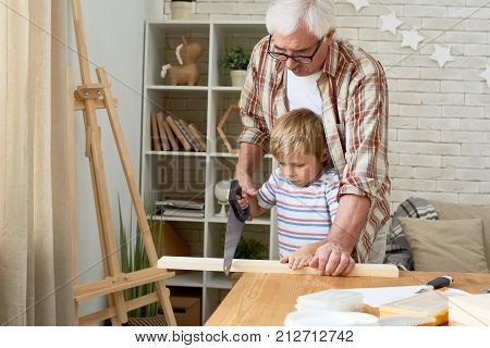 Portrait of nice grandfather teaching grandson woodwork, helping little boy saw piece of wood while making wooden models together poster